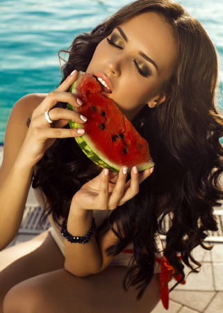 fashion outdoor photo of beautiful sexy woman with dark hair in swimsuit eating watermelon beside swimming pool