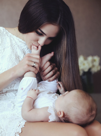 tender photo of beautiful young mother with long dark hair posing with her little adorable baby, mom kissing baby feets photo