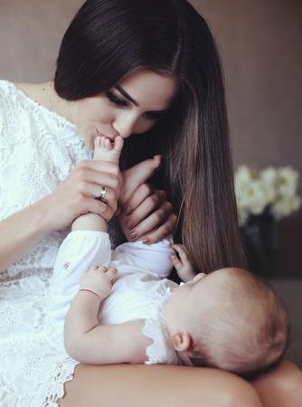 pie bebe: tierna foto de madre hermosa joven con el pelo largo y oscuro que presenta con su pequeño bebé adorable, mamá besando pies del bebé