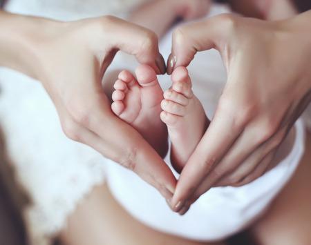 엄마 손에 귀여운 아기의 feets의 간 사진을 부드러운 심장 모양을 유지