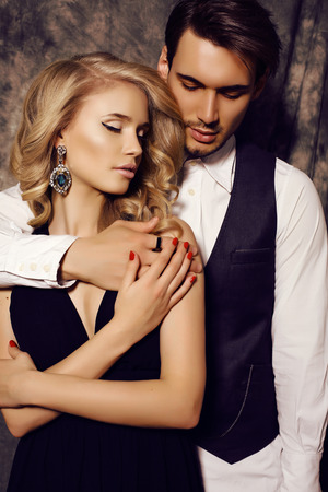 sexual relations: fashion studio photo of beautiful sensual couple in elegant clothes