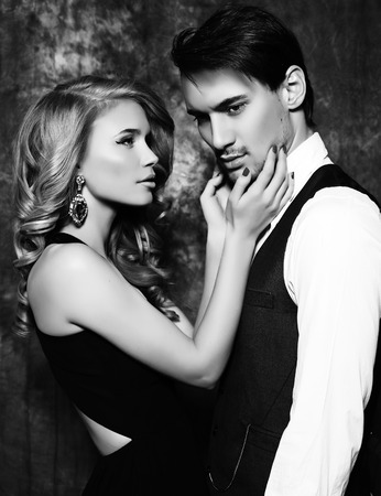 black and white fashion studio photo of beautiful sensual couple in elegant clothes
