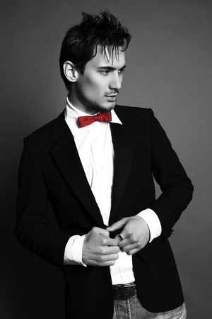 businesslike: black and white fashion studio photo of handsome businesslike man with dark hair in elegant suit