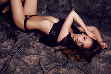 lingerie model: fashion studio photo of beautiful sensual girl with long dark hair wearing black lace lingerie Stock Photo