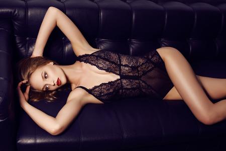 divan: estudio de moda foto de la hermosa chica sensual con el pelo largo y oscuro con la lencer�a de encaje de lujo, acostado en el div�n de cuero negro Foto de archivo
