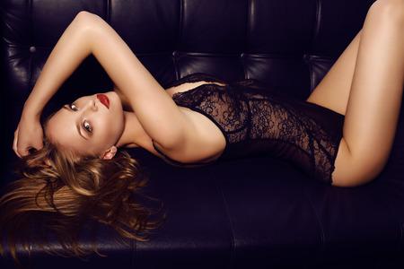 divan: fashion studio photo of beautiful sensual girl with long dark hair wearing luxurious lace lingerie, lying on black leather divan