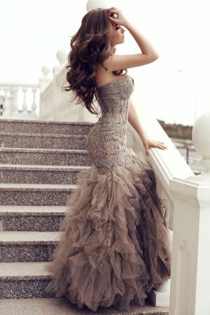 All'aperto foto di moda di bella donna sensuale con lunghi capelli scuri in abito di paillettes di lusso in posa sulle scale Archivio Fotografico - 40439309