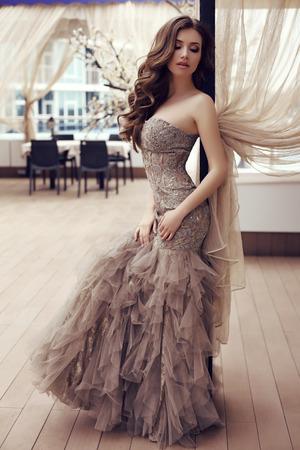 all'aperto foto di moda di bella donna sensuale con lunghi capelli scuri in posa lussuoso abito di paillettes in caffè di estate all'aperto