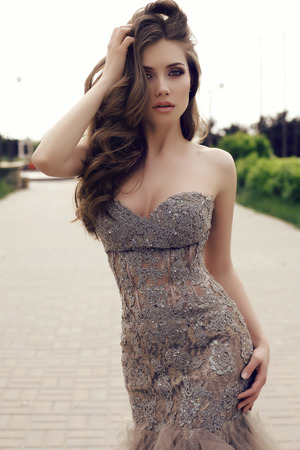 brunette: fashion outdoor photo of beautiful sensual woman with long dark hair in luxurious sequin dress posing in summer park