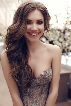 sensual: fashion outdoor photo of beautiful sensual woman with long dark hair in luxurious sequin dress posing in summer outdoor cafe Stock Photo