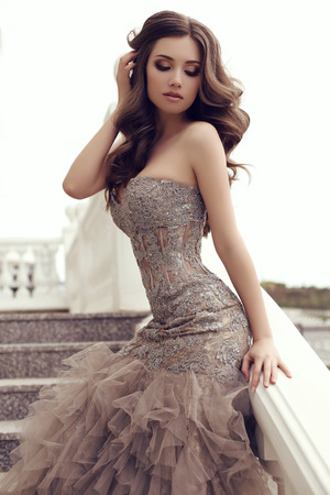 moda foto al aire libre de la mujer hermosa sensual con el pelo largo y oscuro en lujoso vestido de lentejuelas posando en las escaleras