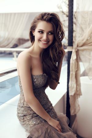 sensual: moda foto al aire libre de la mujer hermosa sensual con el pelo largo y oscuro en lujoso posando vestido de lentejuelas en verano caf� al aire libre