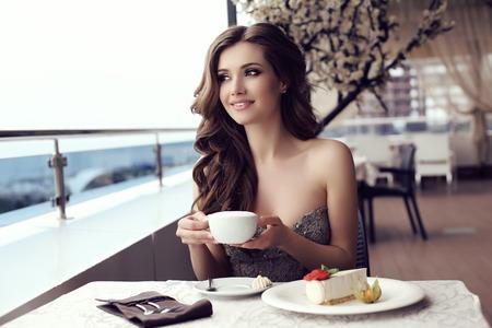 sensual: moda foto al aire libre de la mujer hermosa sensual con el pelo largo y oscuro en lujoso posando vestido de lentejuelas de verano al aire libre cafedrinking un caf�