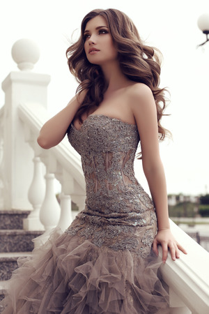 fashion outdoor photo of beautiful sensual woman with long dark hair in luxurious sequin dress posing on stairs