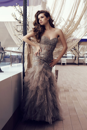 fashion outdoor photo of beautiful sensual woman with long dark hair in luxurious sequin dress posing in summer outdoor cafe Stock Photo