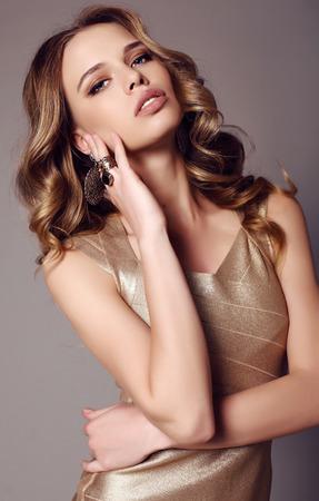 donne eleganti: foto di moda stuidio di bella donna sensuale con i capelli scuri in abito elegante d'oro