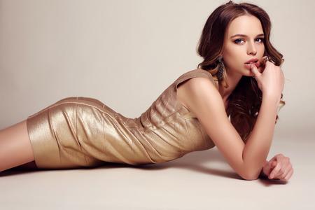 mujer elegante: estudio de moda foto de la hermosa mujer sensual con el pelo oscuro vestido de oro elegante