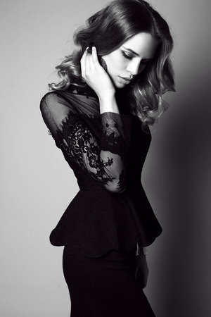 Schwarz-Weiß-Mode-Studio-Foto der schönen sinnliche Frau mit dunklen Haaren in einem eleganten schwarzen Kleid Standard-Bild