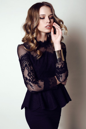 fashion studio photo of beautiful sensual woman with dark hair in elegant black dress