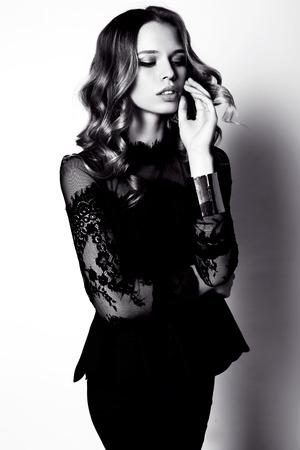 donne eleganti: in bianco e nero di moda foto di studio di bella donna sensuale con i capelli scuri in elegante abito nero Archivio Fotografico