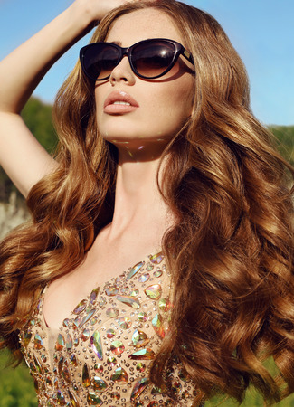 fashion outdoor photo of beautiful sensual woman with long red hair in luxurious sequin dress with sunglasses posing in spring garden