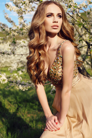 fashion outdoor photo of beautiful sensual woman with long red hair in luxurious sequin dress posing in spring blossom garden