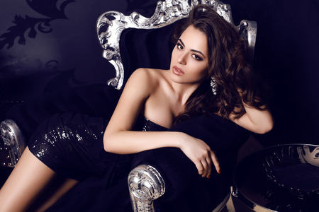fashion photo of gorgeous woman with long dark hair in elegant dress posing in luxurious interior