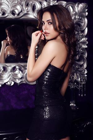 fashion photo of gorgeous woman with dark hair  in elegant black dress posing in luxurious interior