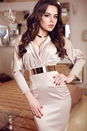 fashion photo of gorgeous woman with dark hair  in elegant dress posing in luxurious interior