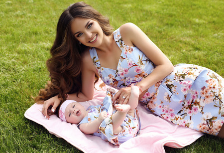 belle brunette: mode photo en plein air de la belle famille mère look.beautiful avec de longs cheveux noirs posant avec son mignon petit bébé dans des robes similaires avec des fleurs Imprimer Banque d'images