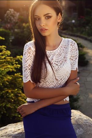 mujeres fashion: moda foto al aire libre de la muchacha hermosa con el pelo oscuro con ropa elegante posando en el jardín de verano