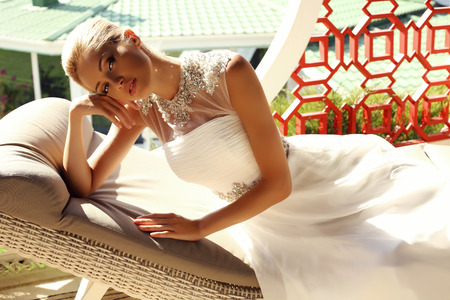 divan: fashion outdoor photo of beautiful sexy girl with blond hair in elegant wedding dress lying on divan in garden house Stock Photo