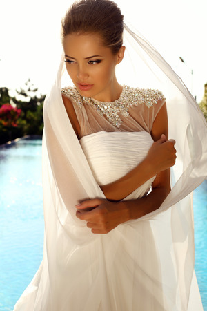 fashion outdoor photo of beautiful sexy girl with blond hair in elegant wedding dress posing  beside a swimming pool