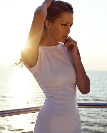 modelos posando: moda foto al aire libre de la hermosa chica sexy con el pelo rubio en elegante vestido posando en yate