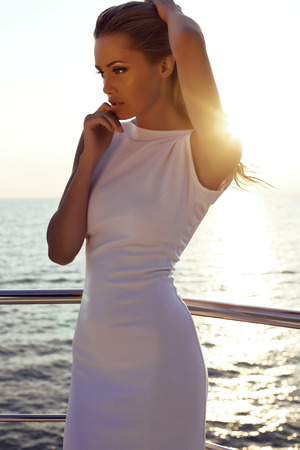 fashion outdoor photo of beautiful sexy girl with blond hair in elegant dress posing on yacht