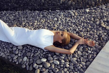 wet dress: fashion outdoor photo of beautiful sexy girl with blond hair in elegant dress posing beside a metallic wall, lying on stones