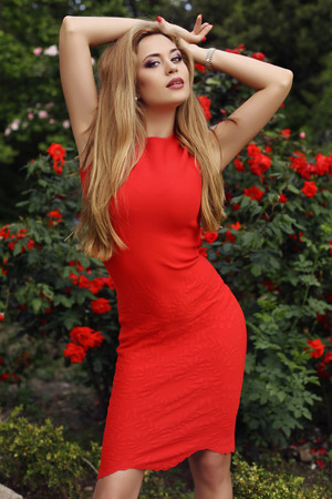 wall watch: fashion outdoor photo of beautiful sexy girl with blond hair in elegant dress posing beside roses wall in summer park Stock Photo