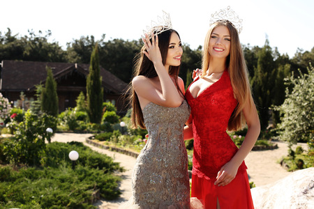 brunette girl: fashion outdoor photo of beautiful girls with long straight hair wearing elegant dresses and luxurious crown posing in summer garden Stock Photo