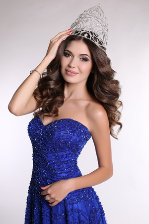 beauty contest: fashion studio photo of gorgeous winner of beauty contest wearing luxurious sequin dress and precious crown Stock Photo