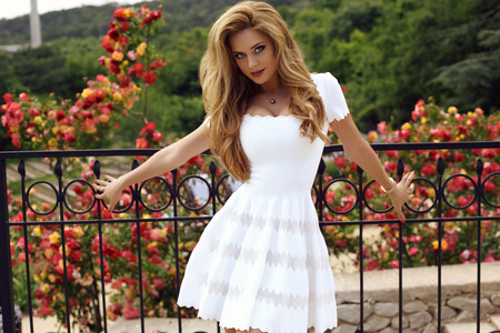 fashion outdoor photo of beautiful sexy girl with blond hair in elegant dress posing  in summer park Stock Photo