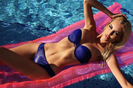 fille nue sexy: mode photo en plein air de la magnifique femme sexy avec les cheveux blonds dans l'élégant bikini bleu de détente dans la piscine de swiming