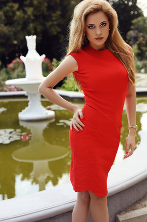 sexy dress: fashion outdoor photo of beautiful sexy girl with blond hair in elegant red dress posing beside an antic fountain in summer park