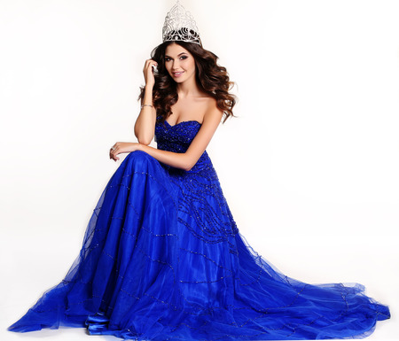 fashion studio photo of gorgeous winner of beauty contest wearing luxurious sequin dress and precious crown Фото со стока