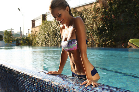 young girls breast: fashion photo of sexy beautiful girl with blond hair in elegant bikini relaxing in swimming pool
