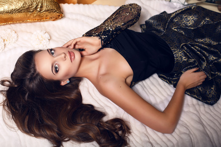 fashion studio photo of beautiful young woman with dark hair in elegant dress posing in bedroom