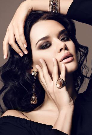 fashion studio photo of beautiful sensual woman with dark hair and bright makeup,with bijou