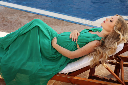 fashion outdoor photo of beautiful pregnant woman with long blond hair in elegant dress posing beside swimming pool Stock Photo