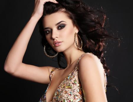 maquillage: studio photo de mode de la belle femme sensuelle avec des cheveux noirs et maquillage lumineux vêtu de la robe à paillettes de luxe