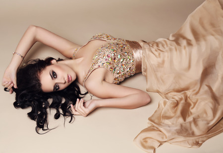 sequin: fashion studio photo of beautiful sensual woman with dark hair and bright makeup wearing luxurious sequin dress