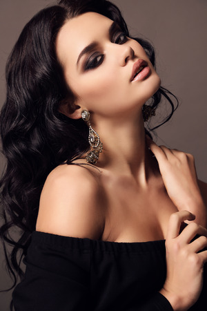 fashion studio photo of beautiful sensual woman with dark hair and bright makeup,with bijou